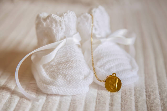 Bootees and a gold chain symbols of a christening of the baby