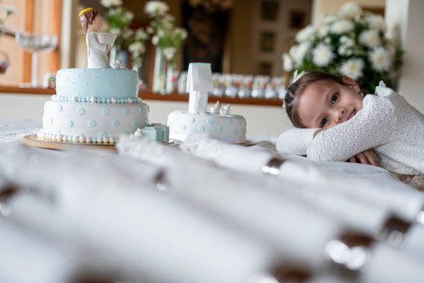 5-year-old Latin girl dressed in an elegant formal dress is inside the house where the celebration of the christening of a baby is held, she rests her head on the central table of the decoration where the cake and cutlery are located, she looks at the camera and smiles